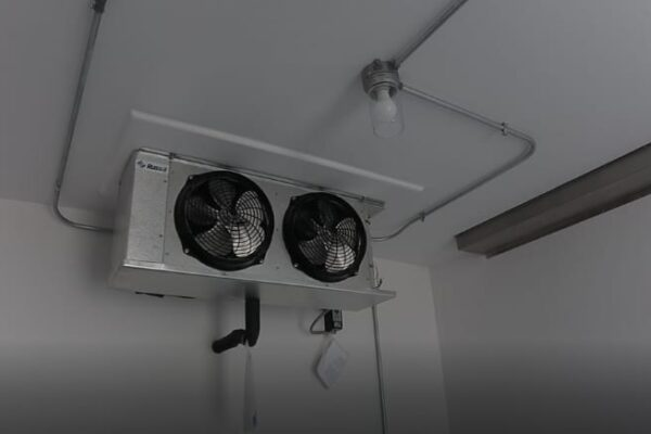 Two black fans on the interior of a walk in refrigeration unit