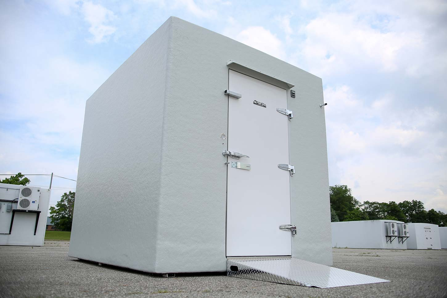 White walk-in cooler freezer combo on concrete