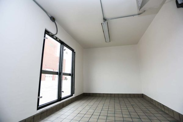 Inside of a refrigeration unit with tile floors and white walls