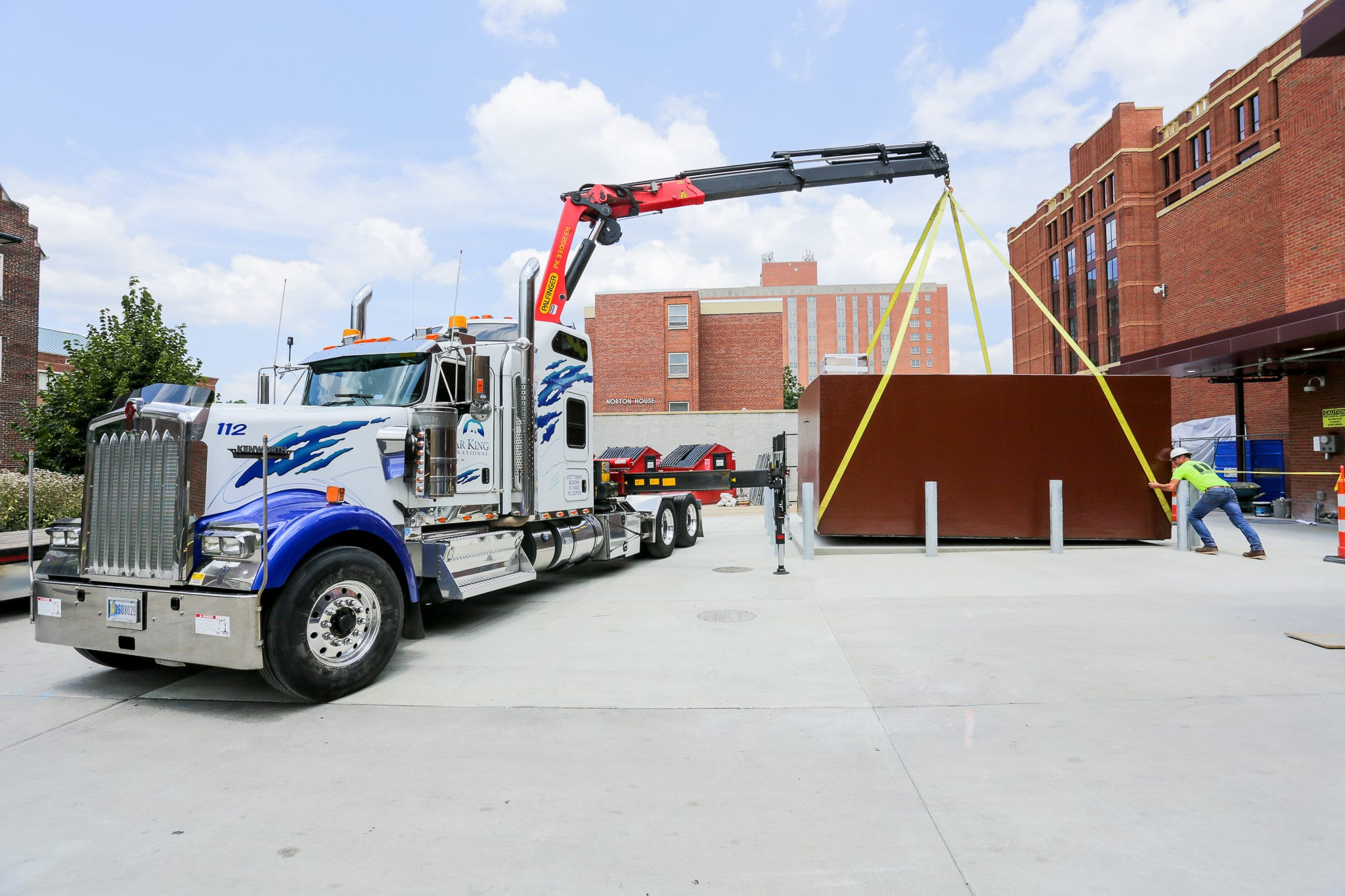 Large semi truck and a crane moving a cooler unit