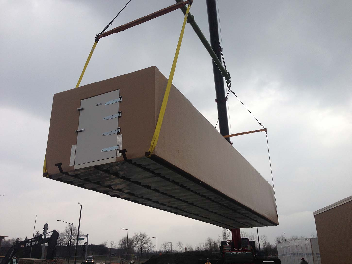 Crane lifting a tan colored walk in freezer for delivery