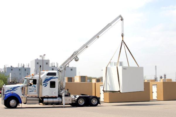 A crane on a semi truck lifting a custom cold room